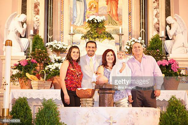 Hispanic family smiling by religious relics