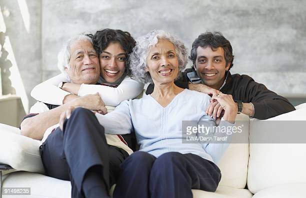 Hispanic family smiling on sofa