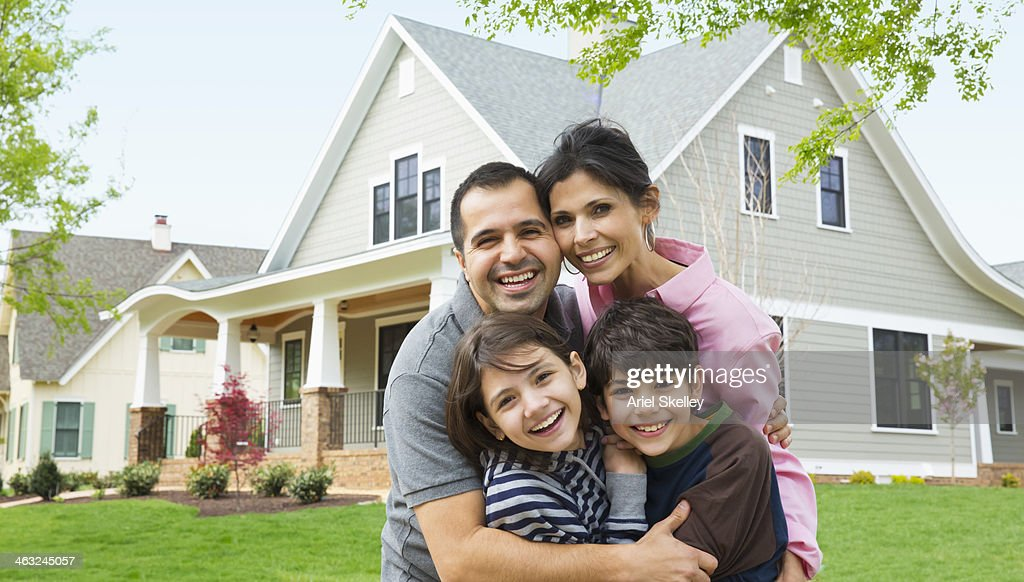 Hispanic family smiling outside house : Stock-Foto