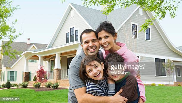 Hispanic family smiling outside house