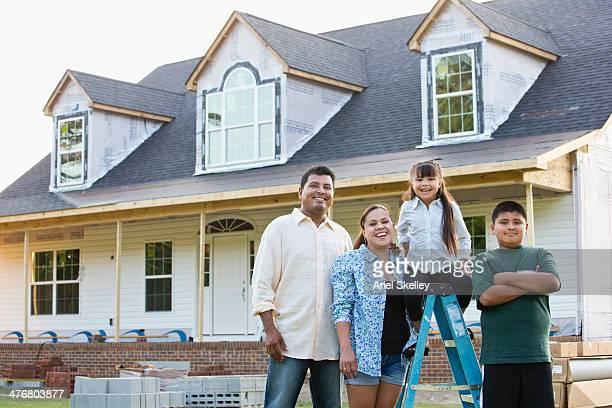 hispanic family smiling outside house under construction - virginia amerikaanse staat stockfoto's en -beelden
