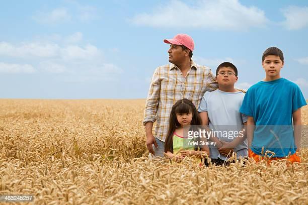 Hispanic family standing in wheat field