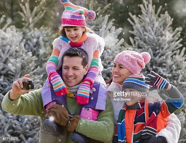 Hispanic family taking own photograph in snow