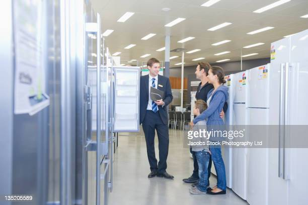 hispanic family talking to salesman in appliance department - electronics store stock photos and pictures