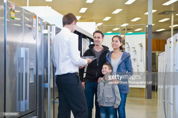 Hispanic family talking to salesman in appliance department