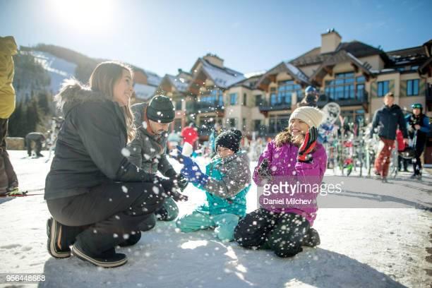 hispanic family throwing snow and having fun on a nice sunny day at a ski resort. - vail colorado fotografías e imágenes de stock
