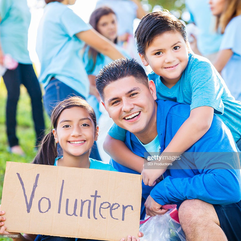 Hispanic Family Volunteer At Park Clean Up Event Stock Photo