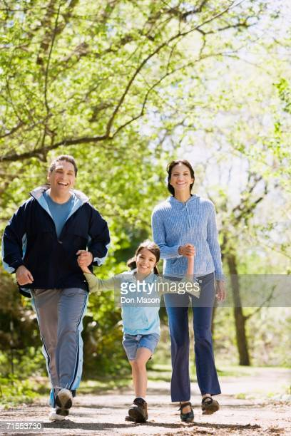 hispanic family walking outdoors - striding stock pictures, royalty-free photos & images