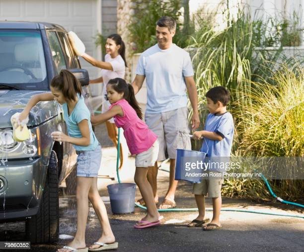 hispanic family washing car - daily bucket stock pictures, royalty-free photos & images