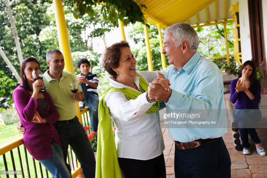 Hispanic family watching senior parents dancing : Stock Photo