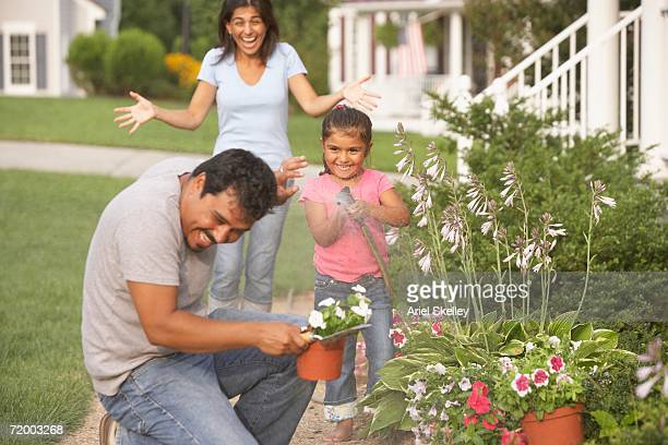 Hispanic family watering garden and playing with hose outdoors