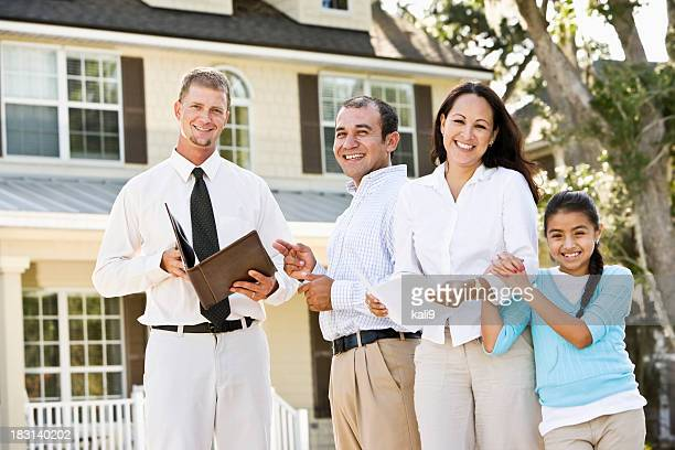 Hispanische Familie mit Immobilienmakler in front of house
