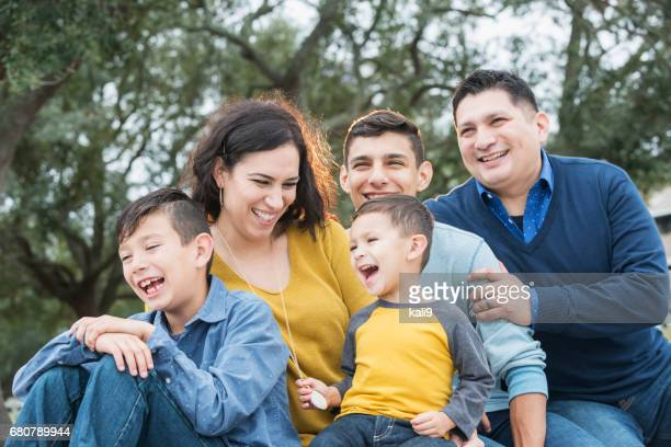 Hispanic family with three boys laughing