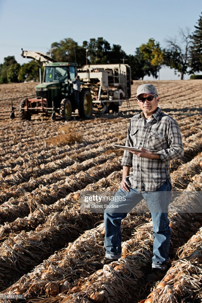 Hispanic farmer using tablet computer in crop field : Stock Photo