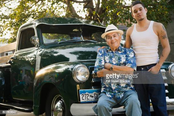 Hispanic father and adult son in front of car