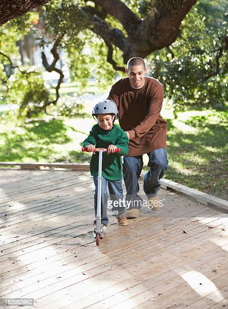 Hispanic father and boy on scooter in park