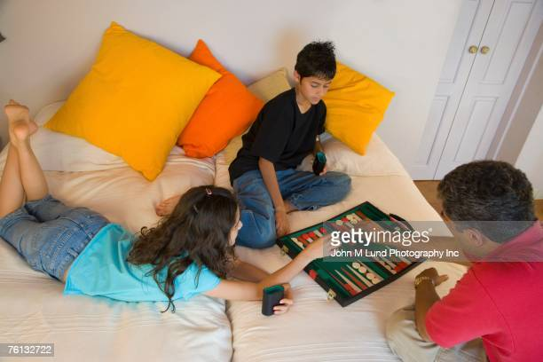 Hispanic father and children playing board game