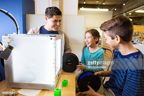 Hispanische Vater UND Kinder mit 3D Drucker im makerspace