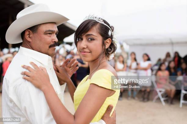 Hispanic father and daughter dancing at quinceanera
