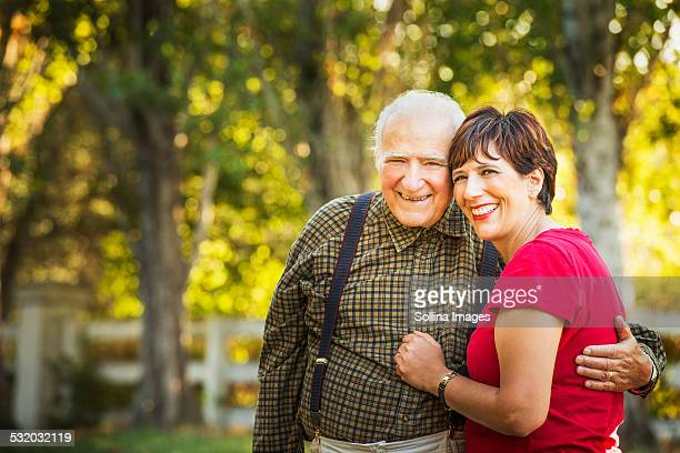 Hispanic father and daughter hugging outdoors