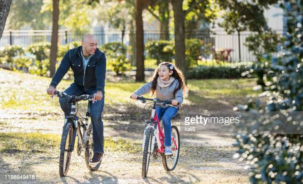 hispanic father and daughter riding bicycles - side by side stock pictures, royalty-free photos & images