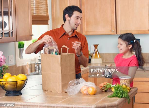 Hispanic father and daughter unpacking groceries in kitchen