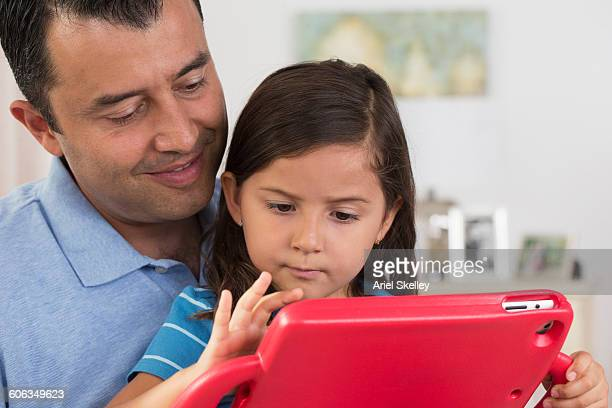 Hispanic father and daughter using digital tablet