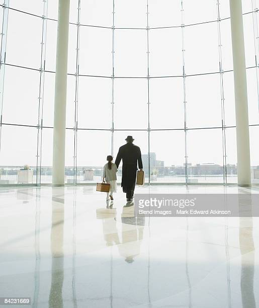 Hispanic father and daughter walking in airport
