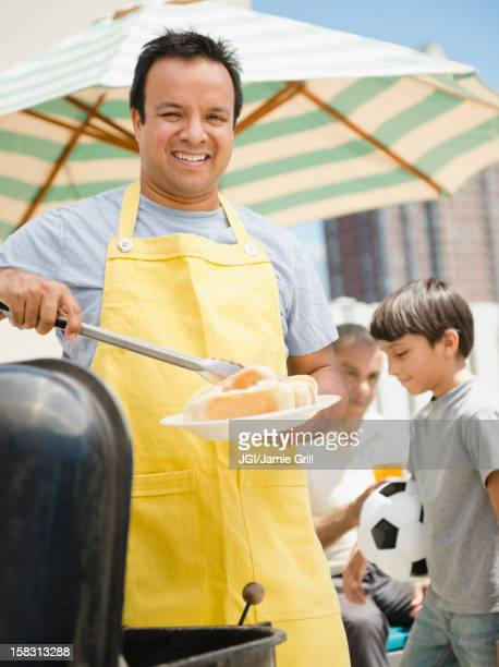 Hispanic father and son at barbecue