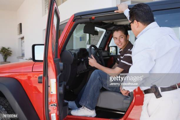 hispanic father and son looking at new cars - test drive stock pictures, royalty-free photos & images