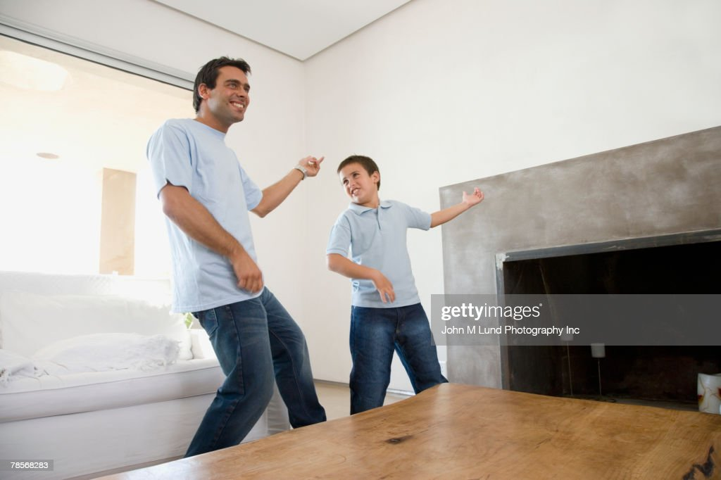 Hispanic father and son playing air guitar : Stock Photo