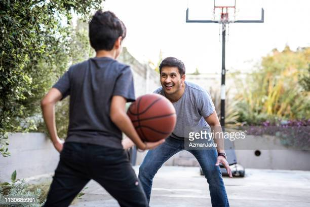 hispanic father and son playing basketball in the backyard - termine sportivo foto e immagini stock