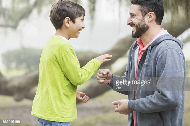 Hispanic father and son playing rock paper scissors