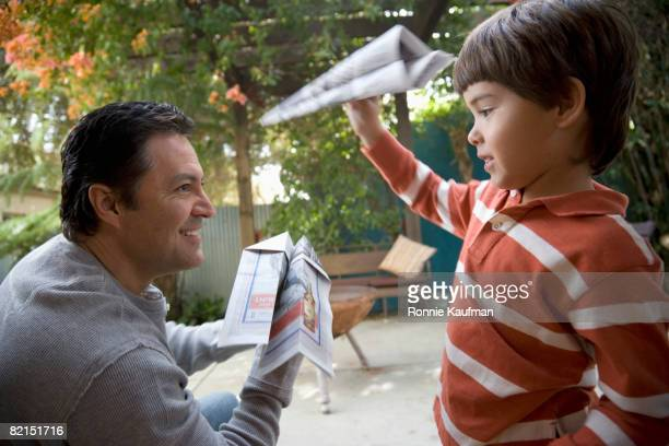 Hispanic father and son playing with paper airplanes