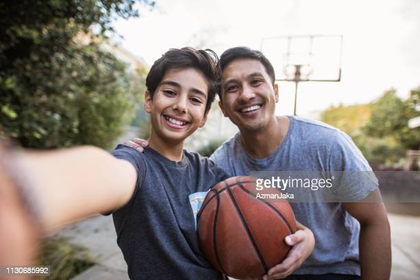 hispanic father and son taking a selfie outdoors whilst playing basketball - drive ball sports stock pictures, royalty-free photos & images
