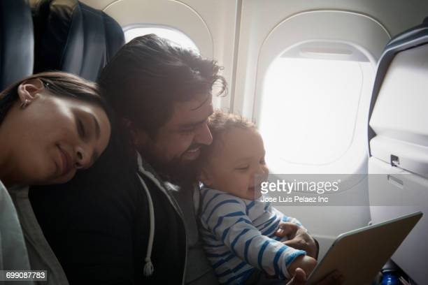 Hispanic father and son using digital tablet on airplane