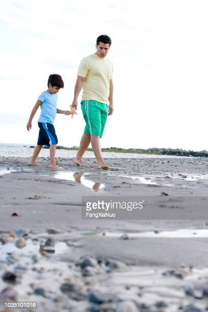 hispanic father and son walking on beach with starfish - westport connecticut stock photos and pictures