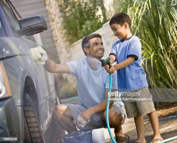 Hispanic father and son washing car