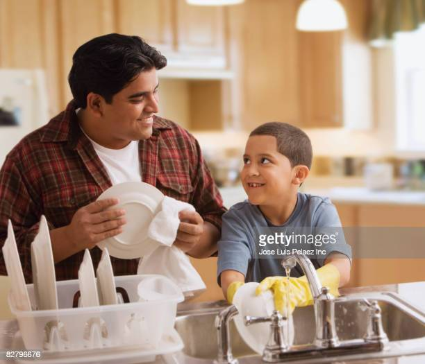 hispanic father and son washing dishes - kids with cleaning rubber gloves stock pictures, royalty-free photos & images