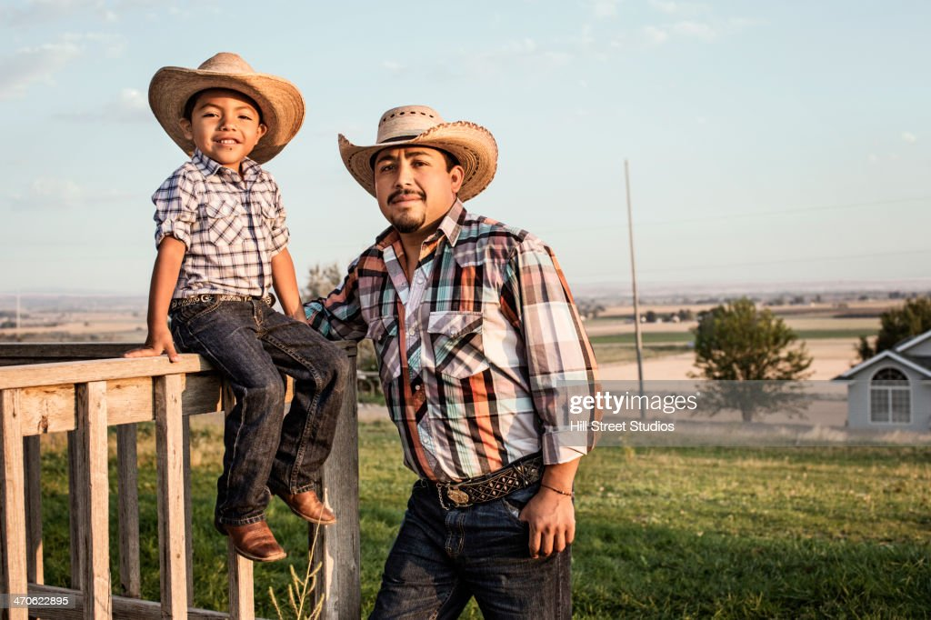 Hispanic father and son wearing cowboy hats outdoors : Stock Photo