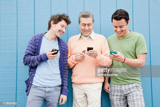 Hispanic father and sons using cell phones outdoors
