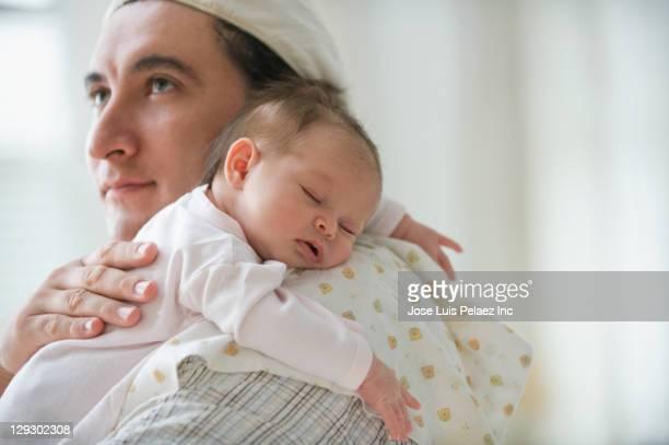 Hispanic father burping newborn baby girl