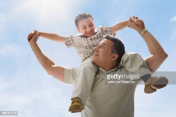 Hispanic father carrying son on shoulders