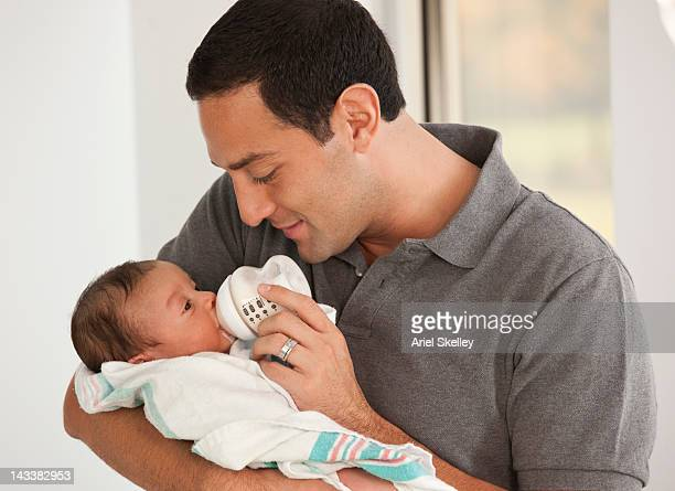Hispanic father feeding newborn baby