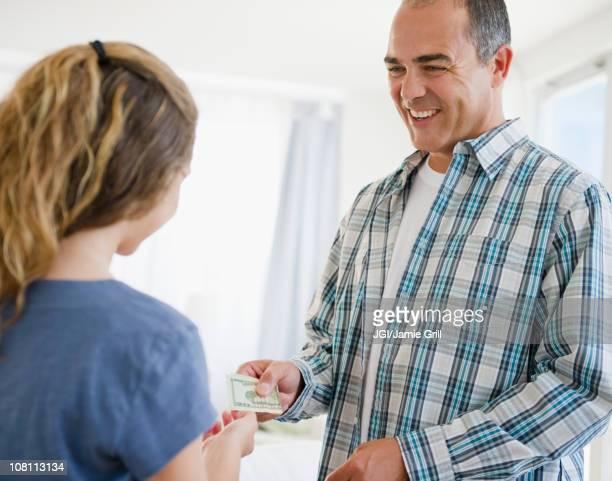 Hispanic father handing daughter money