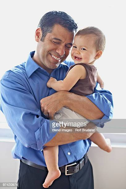 Hispanic father holding daughter