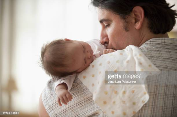 Hispanic father holding newborn baby girl