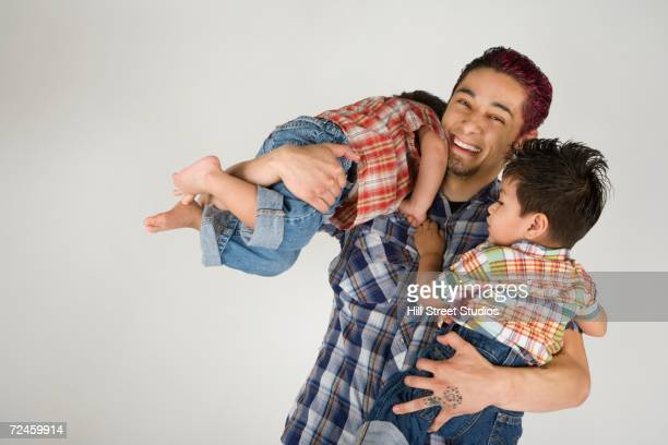 Hispanic father holding toddler children