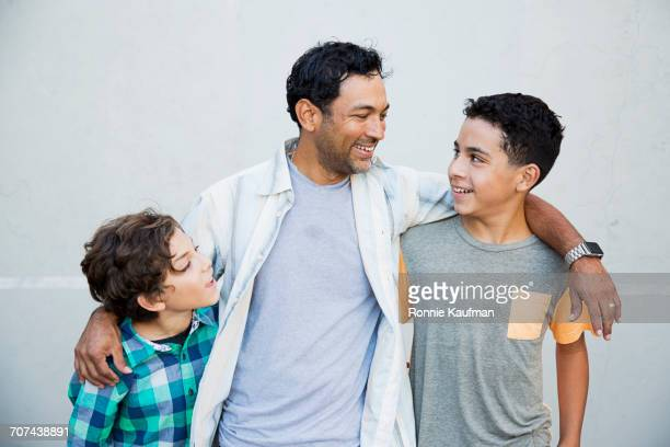 hispanic father hugging sons - pre adolescent child stock pictures, royalty-free photos & images