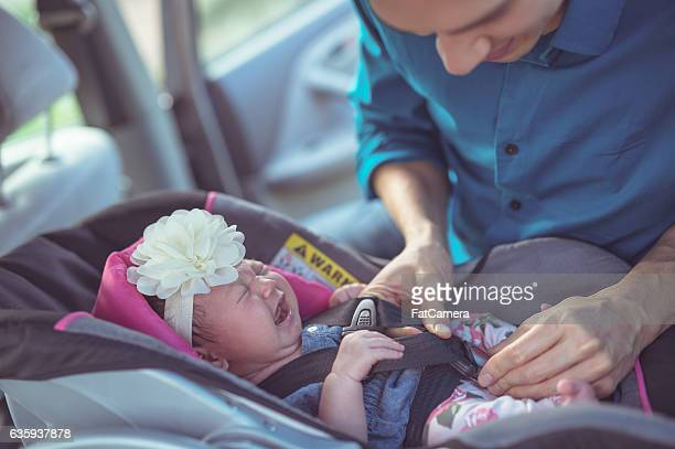 Hispanic father putting his newborn daughter into the carseat